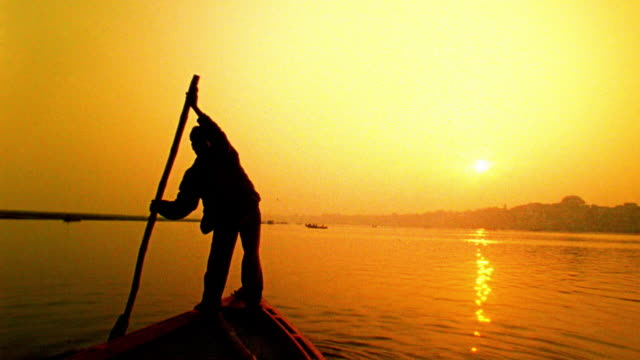 Slow motion wide shot boat point of view with man on bow rowing on Ganges River at sunset / Varanasi, India