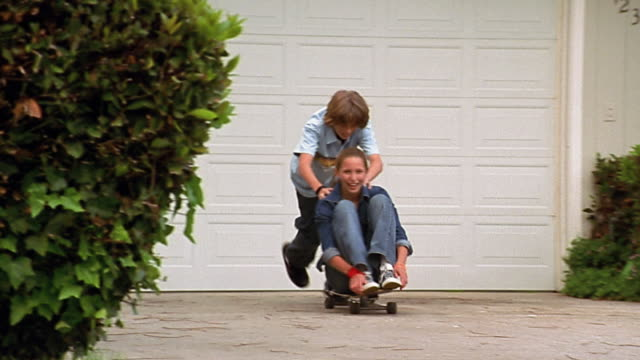 Slow motion wide shot boy pushing girl sitting on skateboard in driveway / crashing and laughing