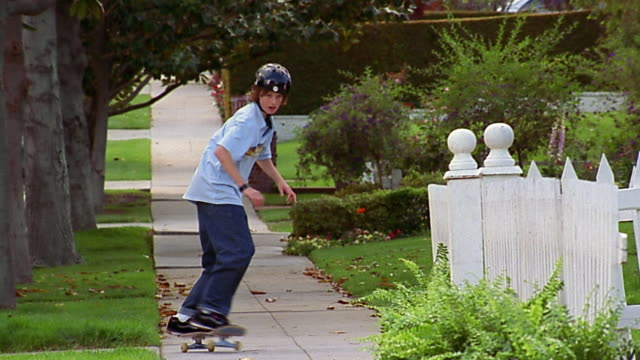Slow motion wide shot boy riding skateboard / doing tricks on sidewalk