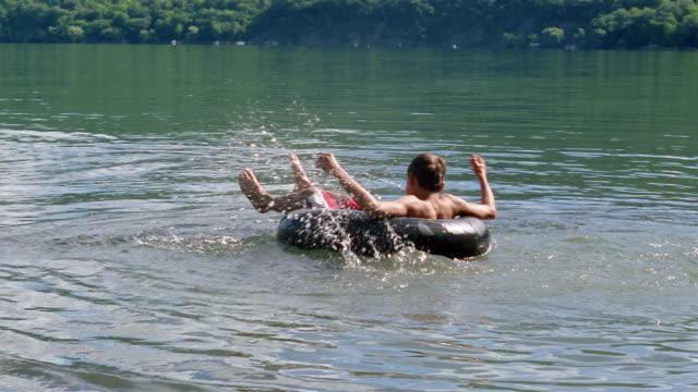 Slow motion wide shot boy spinning around in inner tube on lake / Canandaigua Lake, New York