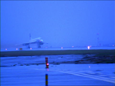 BLUE slow motion wide shot PAN British Airways Concorde jet taking off from airport on rainy day