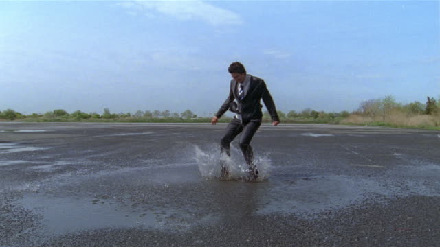 slow motion wide shot businessman jumping and splashing in puddle in empty parking lot - londonalight stock videos and b-roll footage