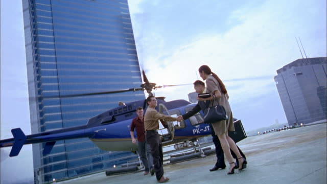 Slow motion wide shot businesspeople shaking hands on building rooftop w/helicopter in background