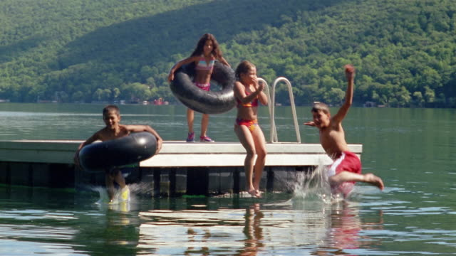 slow motion wide shot children jumping off raft into lake / canandaigua lake, new york - swimming costume stock videos and b-roll footage
