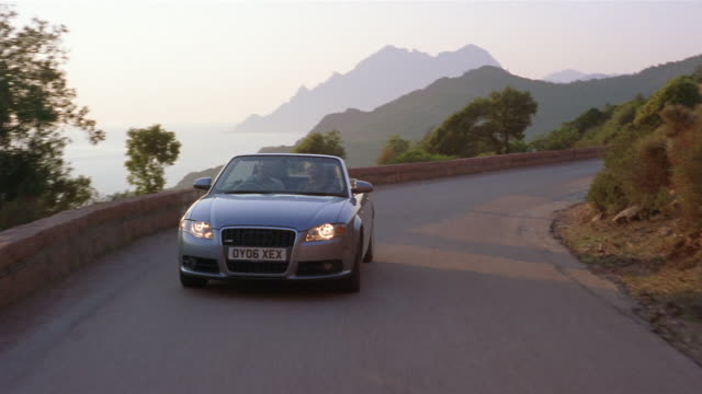 Slow motion wide shot convertible turning on winding mountain road/ Corsica