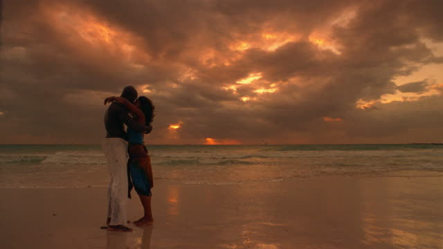 stockvideo's en b-roll-footage met slow motion wide shot couple holding hands walking from water water's edge along beach towards camera / sunset / stopping and kissing / walking back into the water - wide shot