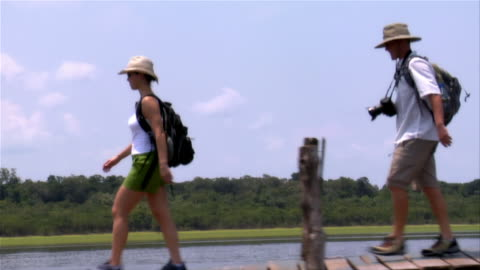 slow motion wide shot couple walking on pier in rio negro/ the amazon, brazil - tracking shot stock videos & royalty-free footage