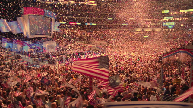 vídeos de stock e filmes b-roll de slow motion wide shot crowds waving american flags with confetti falling at democratic national convention / low angle - comício político