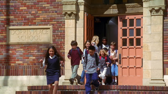 Slow motion wide shot dolly shot teacher opens school door with children exiting and running down stairs past camera