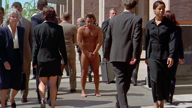 stockvideo's en b-roll-footage met slow motion wide shot embarassed nude man standing on sidewalk / business people walking around him - schaamte