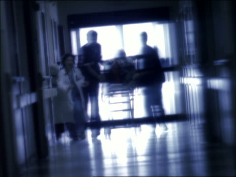 slow motion wide shot emts and medical personnel pushing patient on gurney down hallway, then running - blurred motion stock videos & royalty-free footage
