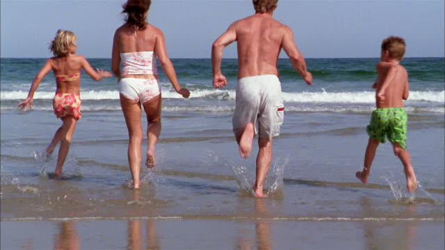 slow motion wide shot family running into surf at beach - サーフパンツ点の映像素材/bロール