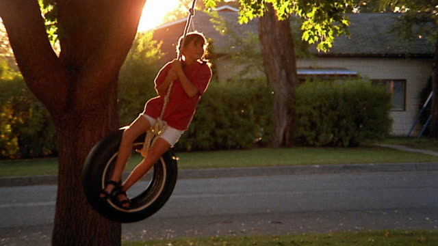 slow motion wide shot girl riding tire swing - tyre swing stock videos & royalty-free footage