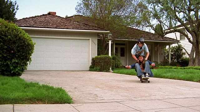 slow motion wide shot girl sitting and boy standing behind her riding on skatebaord in driveway - pushing stock videos & royalty-free footage