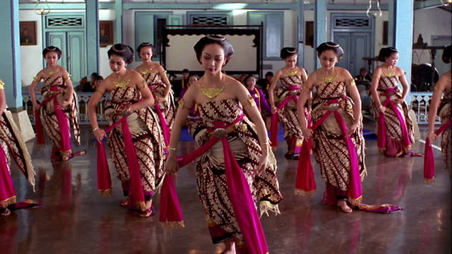 slow motion wide shot group Kraton dancers in costumes on stage / Suryakarta Palace / Solo, Java, Indonesia