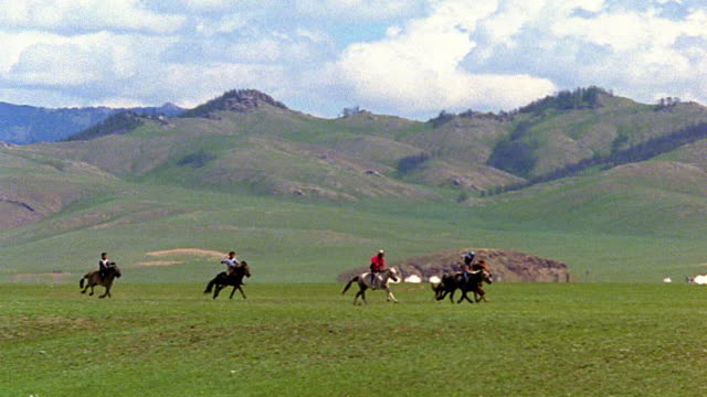 slow motion wide shot PAN group of people on horses running on plain with rolling hills in background / Mongolia