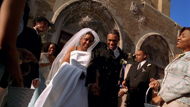 slow motion wide shot guests throwing rice onto black bride and groom coming out of church - hochzeit stock-videos und b-roll-filmmaterial