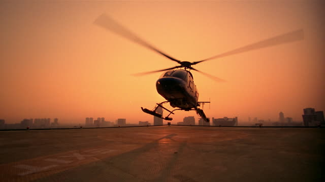 Slow motion wide shot helicopter landing on rooftop helipad at sunrise / tops of skyscrapers in background / Jakarta