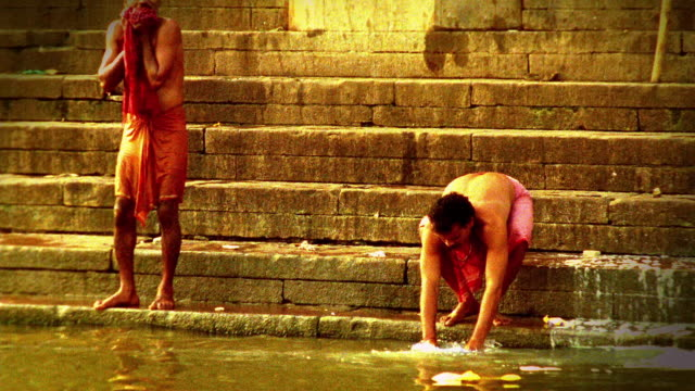 vidéos et rushes de slow motion wide shot indian man on steps washing cloth in ganges while other man washes face / varanasi, india - sale
