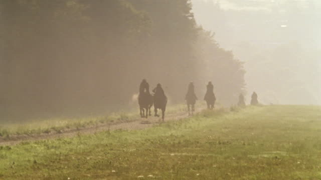 slow motion wide shot jockeys riding horses in fog on dirt track/ berkshire, england - see other clips from this shoot 997 stock videos and b-roll footage