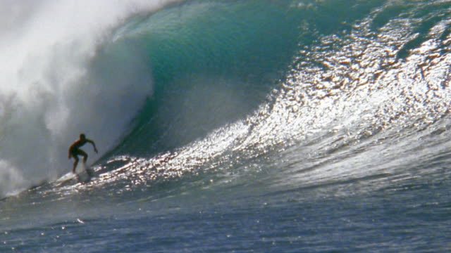 Slow motion wide shot male surfer riding on large wave / riding inside wave / Oahu, Hawaii