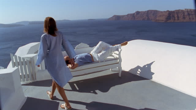 Slow motion wide shot man lounging on terrace with view of Aegean Sea / woman walking past / Santorini, Greece