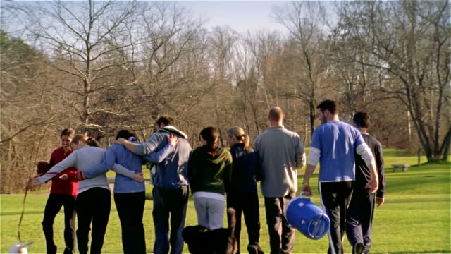 slow motion wide shot men and women walking away with arms around each other following touch football game/ maine - touch football video stock e b–roll