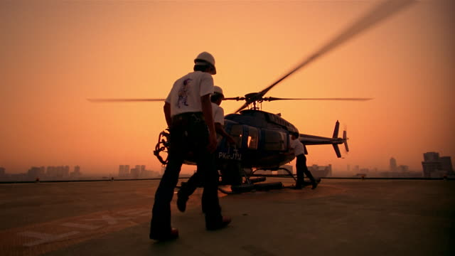 Slow motion wide shot men with hard hats walking up to board helicopter on helipad at sunrise / Jakarta