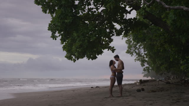 slow motion wide shot of couple kissing on beach / esterillos, puntarenas, costa rica - flirting stock videos & royalty-free footage