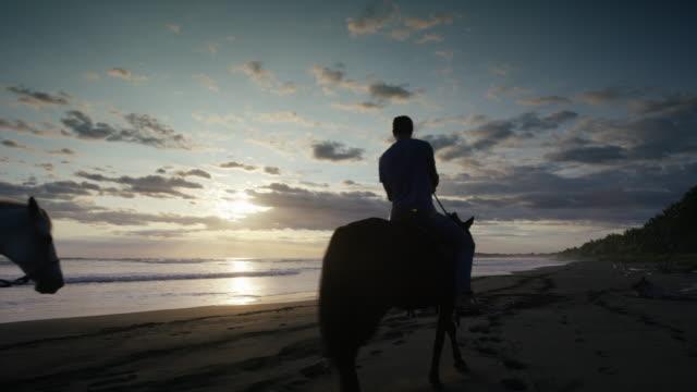 vídeos y material grabado en eventos de stock de slow motion wide shot of couple riding horseback on beach / esterillos, puntarenas, costa rica - equitación