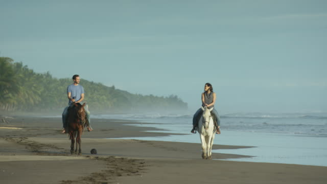 slow motion wide shot of couple riding horseback on beach / esterillos, puntarenas, costa rica - costa rica video stock e b–roll