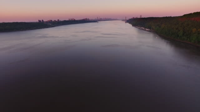 stockvideo's en b-roll-footage met slow motion wide shot of hudson river, soaring toward george washington bridge at sunrise - hudson rivier