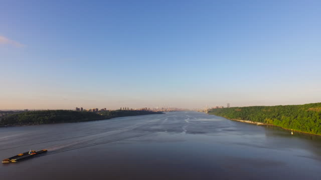 Slow motion wide shot of Hudson River with lone barge at bottom left of frame