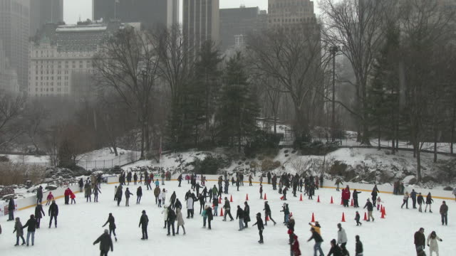 slow motion, wide shot of many people ice skating in wollman rink in central park, new york city on a snowy winter day. - ice skating stock videos & royalty-free footage