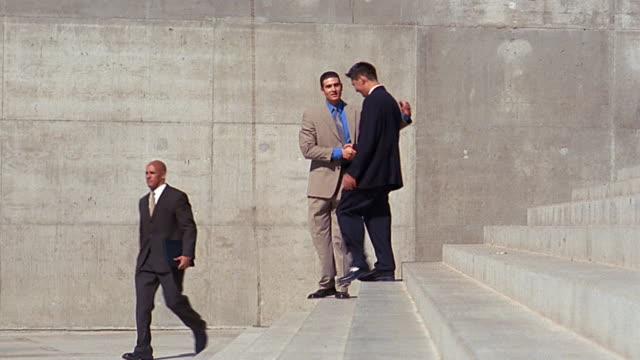 vidéos et rushes de slow motion wide shot pan 2 businessmen meeting on stairs / handshake greeting / walking away - âges mélangés