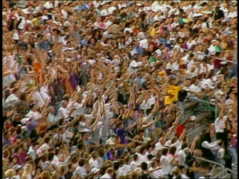 slow motion wide shot pan crowds in stadium bleachers standing and doing 'the wave' - waving stock videos & royalty-free footage