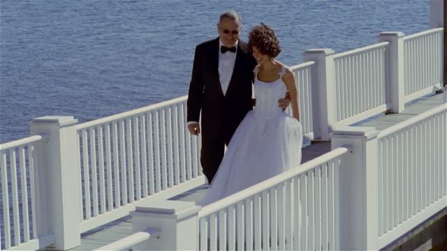 vídeos de stock e filmes b-roll de slow motion wide shot pan father walking bride down pier/ solebury, pennsylvania - pai da noiva