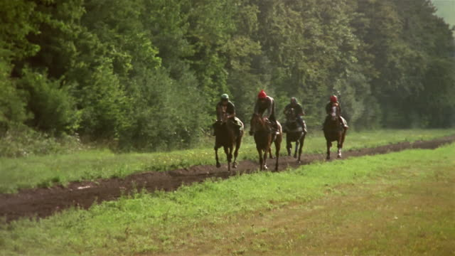slow motion wide shot pan jockeys riding horses on country dirt track/ berkshire, england - see other clips from this shoot 997 stock videos and b-roll footage