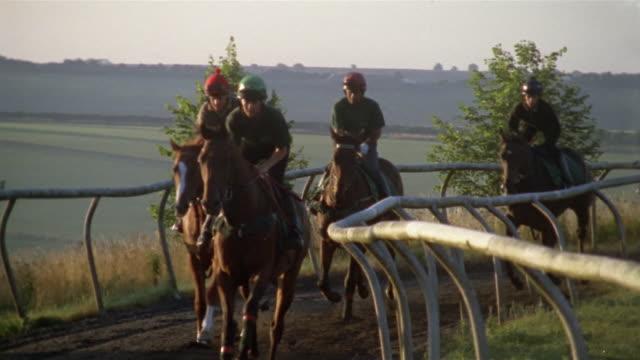 vidéos et rushes de slow motion wide shot pan jockeys riding horses on dirt track/ tilt down horses hooves on dirt track/ berkshire, england - sabot