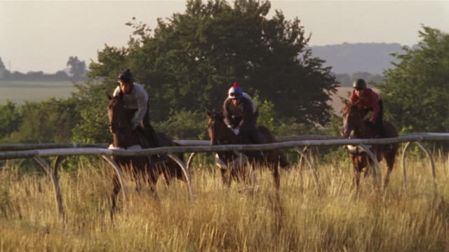 slow motion wide shot pan jockeys riding horses on track/ berkshire, england - see other clips from this shoot 997 stock videos and b-roll footage