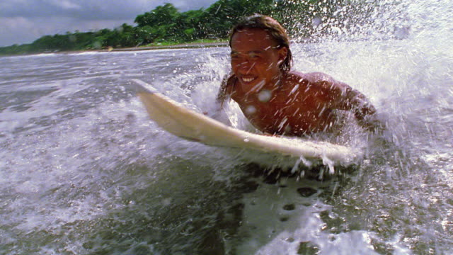 Slow motion wide shot pan surfer leaping face down onto board in water and beginning to paddle / Bali, Indonesia