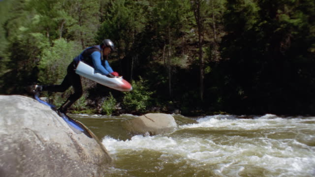 Slow motion wide shot pan two men jumping off rock to begin white water sledging on Roaring Fork River/ Colorado