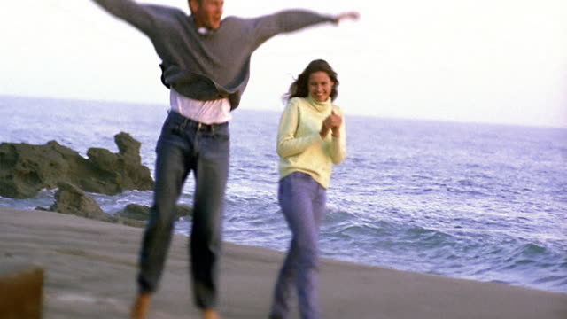 slow motion wide shot pan young man doing cartwheel for young woman, bowing and hugging her on beach / california - cartwheel stock videos & royalty-free footage