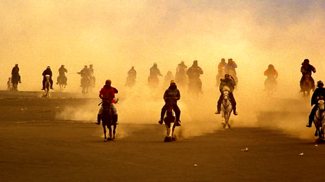 orange slow motion wide shot partly silhouetted people riding horses running across bromo crater / java - bromo crater stock videos & royalty-free footage