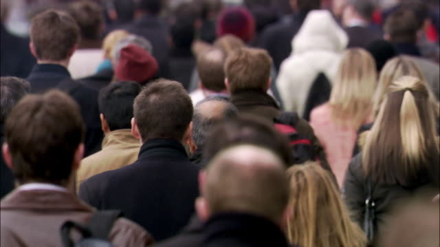 slow motion wide shot pedestrians walking on crowded street - population explosion stock videos & royalty-free footage