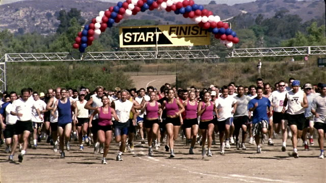 Slow motion wide shot people taking off running at starting line of race