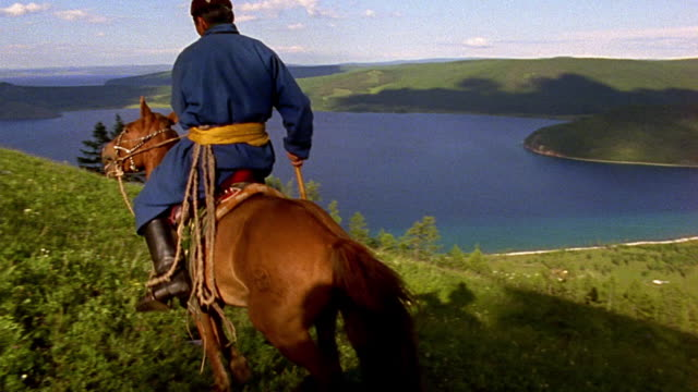 slow motion wide shot PAN REAR VIEW Asian man riding horseback on hillside with lake in background / Mongolia
