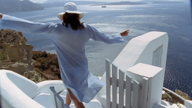 Slow motion wide shot rear view of woman in tunic hopping down stairs with view of Aegean Sea / Santorini, Greece
