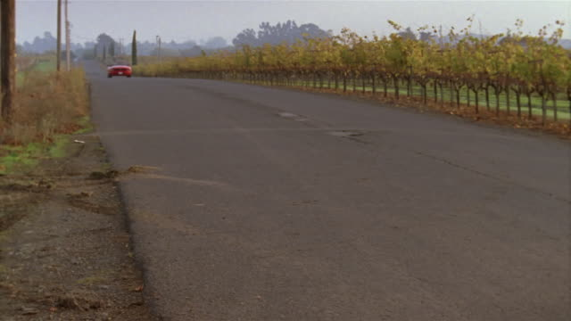 slow motion wide shot red ford mustang convertible driving down road surrounded by vineyards/ woman waving as car goes by/  napa valley, california - mustang convertible stock videos & royalty-free footage