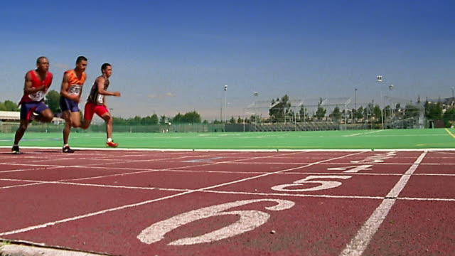 slow motion wide shot runners crossing finish line - linea d'arrivo video stock e b–roll